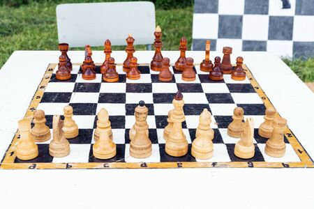 Chess board with wooden figures. Chess tournament outdoors