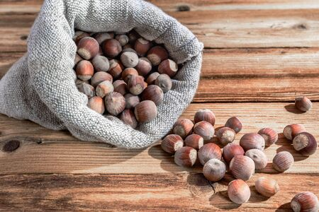 Hazelnut in a sack on a wooden background Standard-Bild