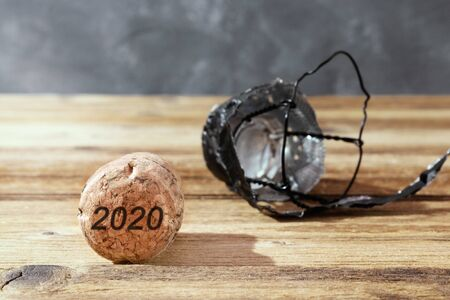 Champagne cork on brown wooden background with numbers 2020. Concept of the New Year