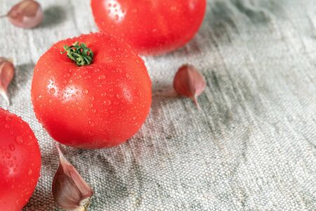 Red ripe tomatoes in drops of water and garlic cloves Imagens