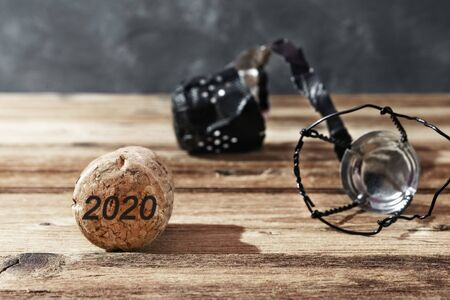 Wooden cork and champagne cap on brown background with date 2020. New year celebration concept 写真素材