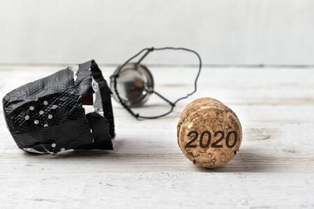 Champagne cork on white wooden background with date 2020. The concept of the New Year