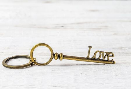 Key with the word love on a white wooden background