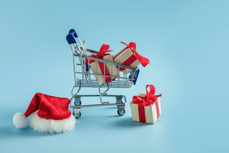 Mini supermarket trolley with gift boxes and red Santa Claus cap on blue background 写真素材