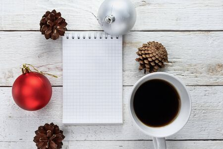 Empty notebook, coffee, fir cone, Christmas ball on a white wooden background