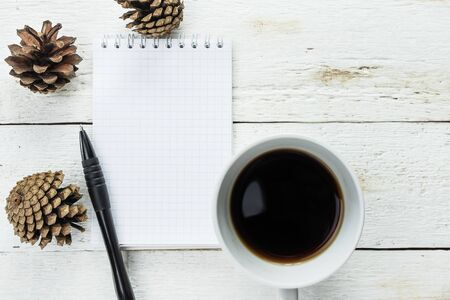 Empty notebook, coffee, fir cones on white wooden background