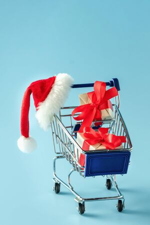 Mini trolley with gift boxes and red Santa Claus cap on blue background 写真素材