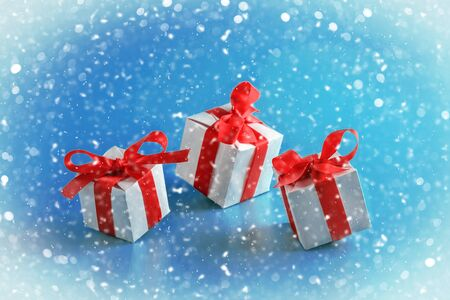 Blue background with Christmas gift boxes. Boxes with red bows on the background of falling white snow