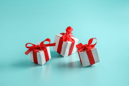 Gift boxes with red bows on a light blue background