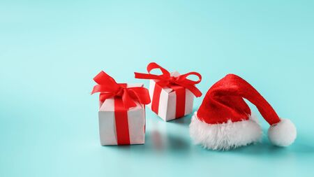 Boxes with red bows and Santa hat on a blue background