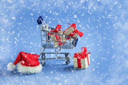 Trolley with gift boxes and Santa hat on blue snow background. Concept: Christmas sale, gifts, delivery, shopping