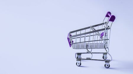 Supermarket trolley on a blue background. Copy space 写真素材