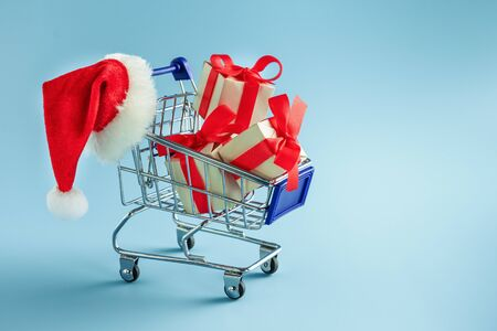 Cart with gift boxes and Santa hat on blue background