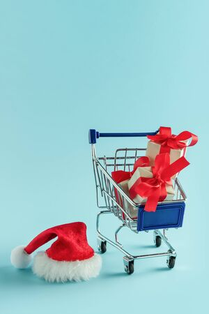 Cart with gifts and Santa hat on blue background