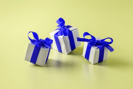 Gift boxes with blue bows on yellow background 写真素材
