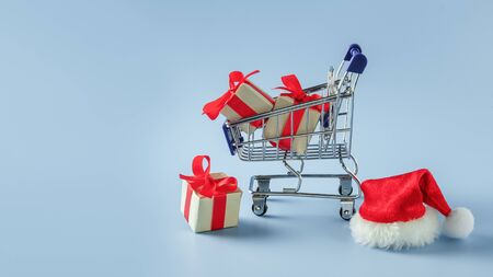 Supermarket cart with boxes and Santa hat on blue background. Concept: Christmas sale, delivery, shopping, gifts