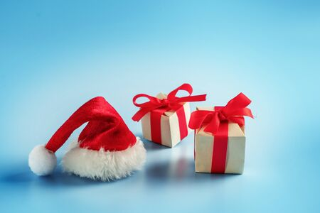 Gift boxes and Santa hat on blue background. Christmas gift
