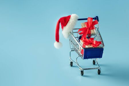 Cart with gift boxes and a red Santa hat on a blue background. Christmas sale