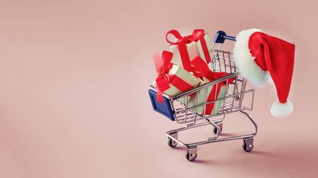 Trolley with gift boxes and red santa hat. on a blue background. Christmas sale 写真素材