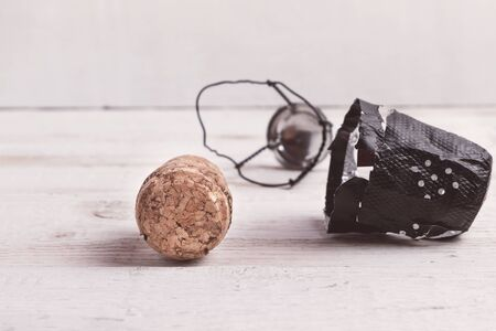Wooden cork and champagne cap on old white background