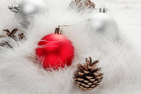 Red and silver Christmas balls and fir cone on white fluff 写真素材