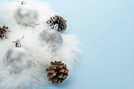 Silver Christmas balls and fir cones on white fluff on blue background