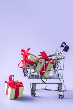 Mini cart with gift boxes with red bows 写真素材
