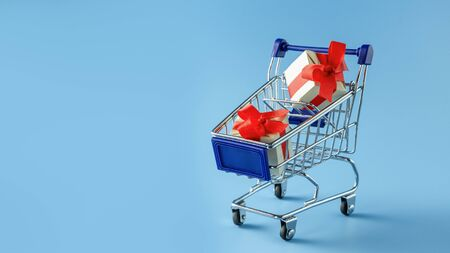 Basket with gift boxes on blue background 写真素材