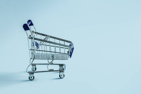 Empty shopping cart on blue background 写真素材