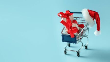 Shopping cart with gift boxes and Santa hat on blue background