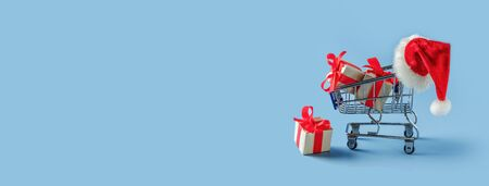 Shopping trolley with gift boxes and santa hat on blue background. Panorama