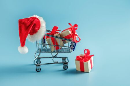 Cart with gift boxes and Santa hat. Blue background with supermarket trolley and boxes with bow