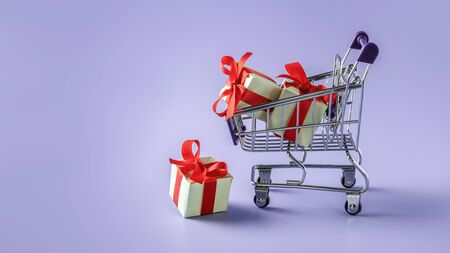 Cart with gift boxes. Background with supermarket trolley and boxes with bow
