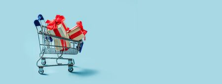 Cart with gift boxes. Blue background with supermarket trolley and boxes with bow