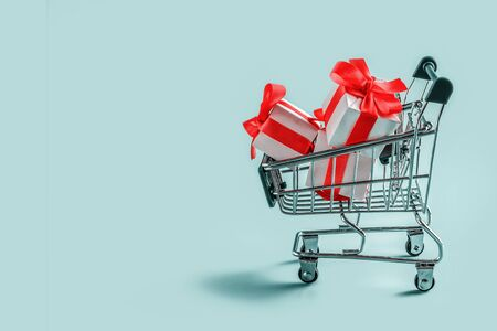 Cart with gift boxes on blue background.