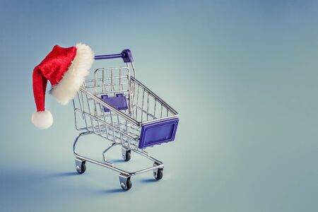 Shopping basket and Santa hat. Christmas shopping concept, sale 写真素材