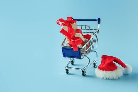 Trolley with gift boxes and santa hat. Christmas shopping concept, clearance sale, gifts 写真素材