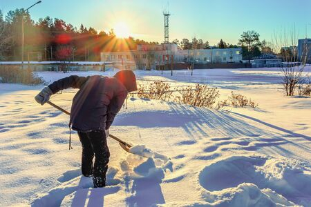 Teenager cleans the road from the snow with a wooden shovel. Sunny frosty winter day 写真素材