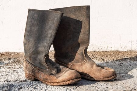 Old worn dirty boots. Shabby torn shoes