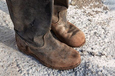 Old worn muddy boots. Old ragged shoes 写真素材