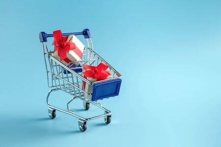 Cart with gifts. Gift boxes in a supermarket cart 写真素材