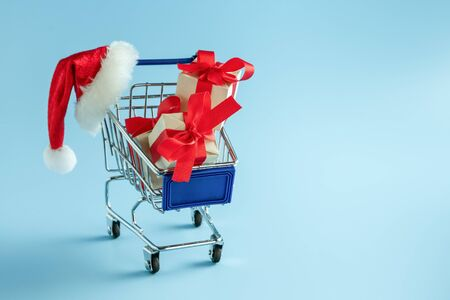 Cart with gifts. Boxes in a supermarket shopping basket. Christmas sale 写真素材