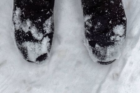 Wet boots on the white snow. Winter suede shoes