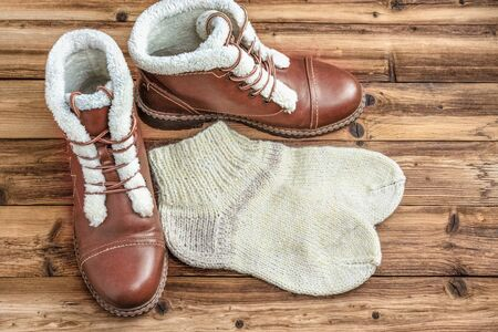 A pair of winter brown boots and knitted warm socks on a wooden background