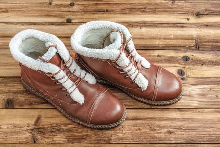 A pair of winter brown boots on a wooden background