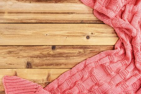 Knitted pink warm blanket on wooden background with space for text. Top view 写真素材