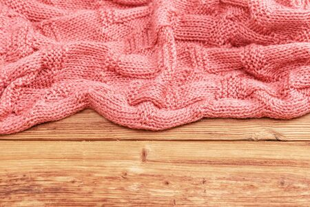Pink knitted soft blanket on wooden background with space for text