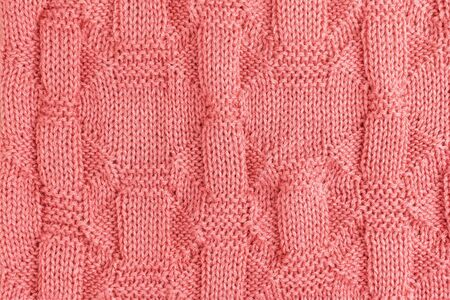 Pink knitted soft blanket. Knitted pink background. Top view