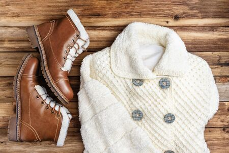 Warm outerwear for women. Knitted white coat and brown boots with fur