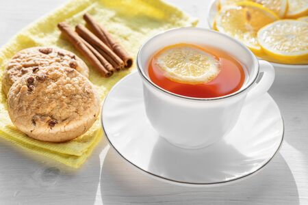 White cup of tea with lemon, cookies and cinnamon